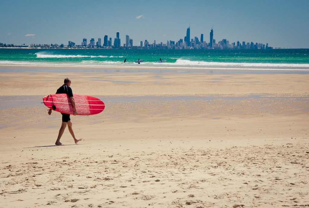 A surfer heading out at Currumbin beach with the Gold Coast skyline in the background